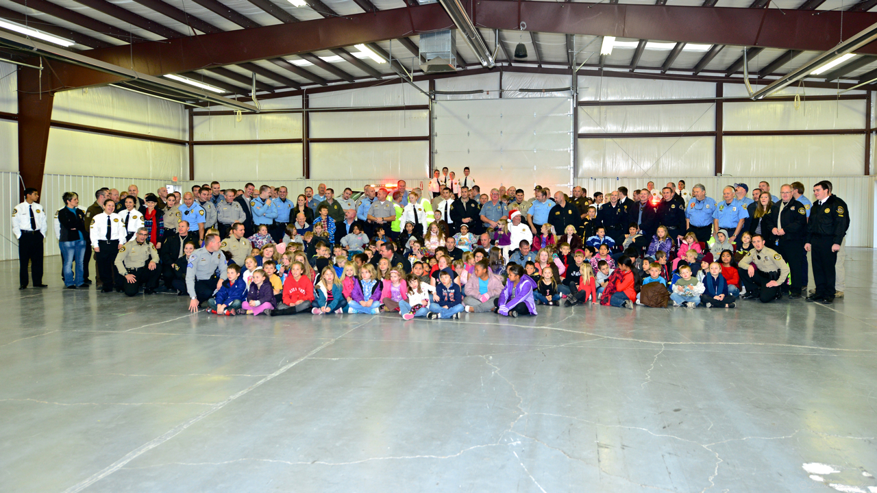 Group photo about 100 children with public safety agencies 2012 Shop with a Cop event.