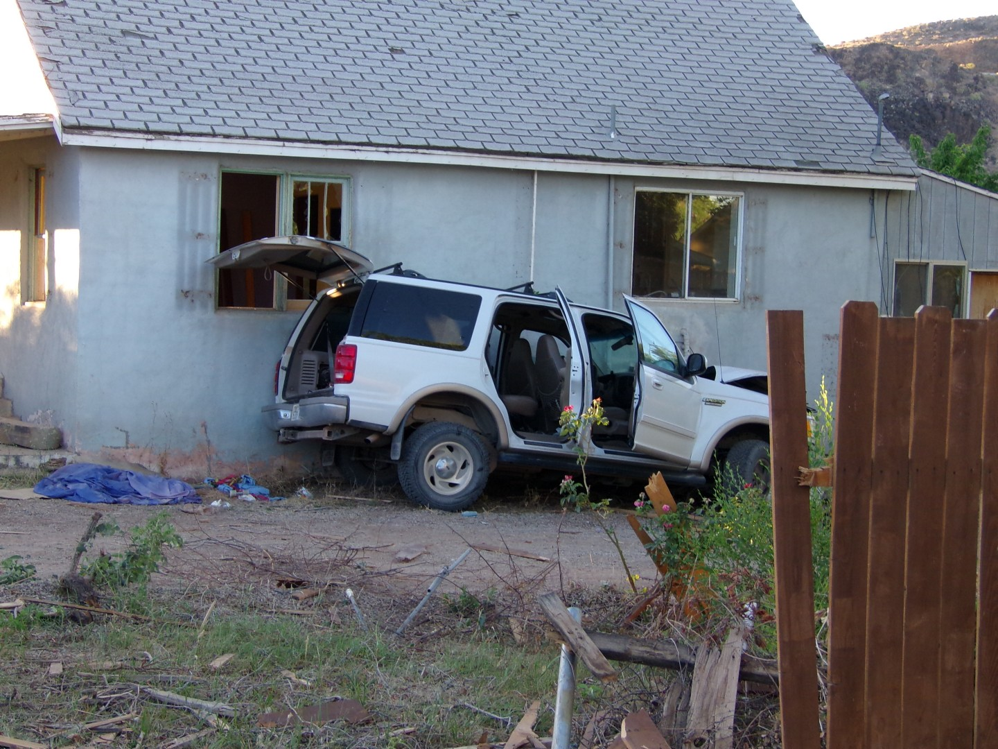 Abandoned vehicle at 150 East 600 North, after driver crashed through the fence and against the house. Hurricane, Utah, June 26, 2013 | Photo by Christina DeMille, St. George News