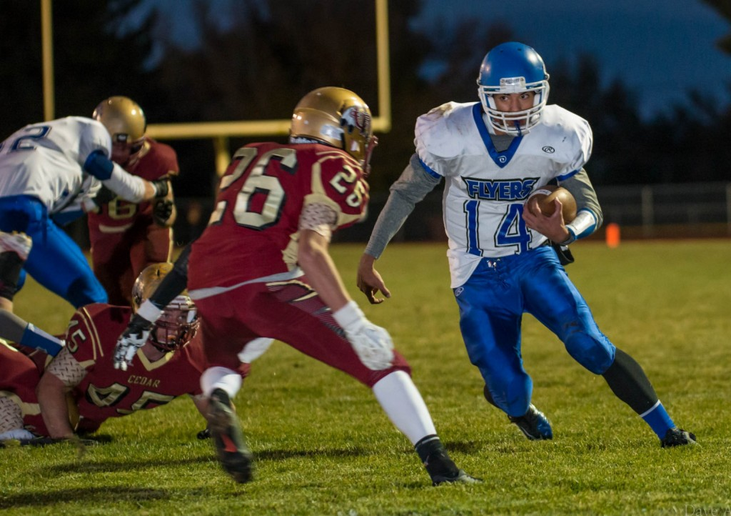 Ammon Takau (14) is pursued by Jeff Rogers (26), Dixie at Cedar, Cedar City, Utah, Oct. 16, 2013 | Photo by Dave Amodt, St. George News