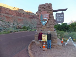 "(L-R) Wendy Harris, a Springdale buisness owner, and Teresa Soper, who drives a park tour bus, stand outside of the entrance of Zion National Park asking whoever will pay attention to help ""save out parks,"" Springdale, Utah, Oct. 1, 2013 