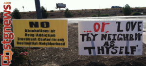 Signs both opposing and supporting a planned drug and alcohol treatment facility stand side-by-side at the Bloomington interchange. Aug. 9, 2013 | Photo by Samantha Aiken, St. George News