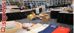 Volunteers sit on the floor and organize merchandise, Huntsman World Senior Games, St. George, Utah, Oct. 5, 2013 | Photo by Zach Windsor, St. George News