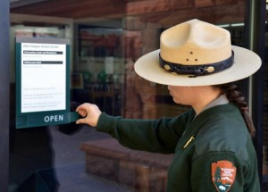 """A park ranger changes the sign on the Zion Canyon Visitor Center to """"open"""" after being closed   as a part of the government shutdown, Zion National Park, Utah, Oct. 1, 2013 