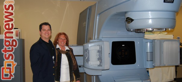R-L: Valley View Medical Center Foundation development officer Michael France and Foundation Board Chair Carolyn Rondthaler standing next to the LINAC machine with the CAT-scan upgrade, made possible by local donations, Cedar City, Utah, December 2013 | Photo courtesy of Valley View Medical Center, St. George News