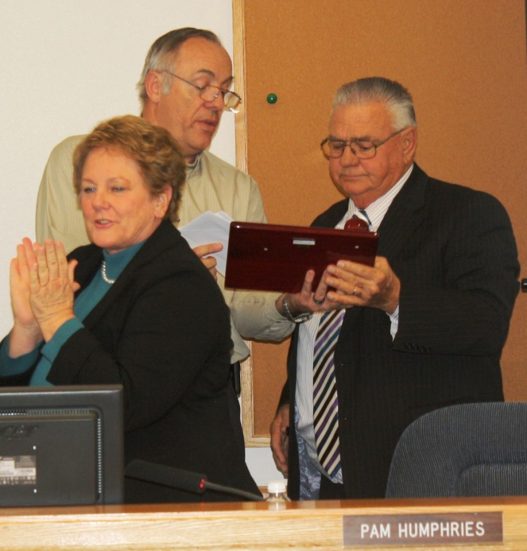 Mayor Tom Hirschi receives plaque from Clark Fawcett while Pam Humphries applauds at Hirschi's last City Council meeting as mayor,  Hurricane, Utah, Jan. 3, 2014 | Photo by Reuben Wadsworth, St. George News
