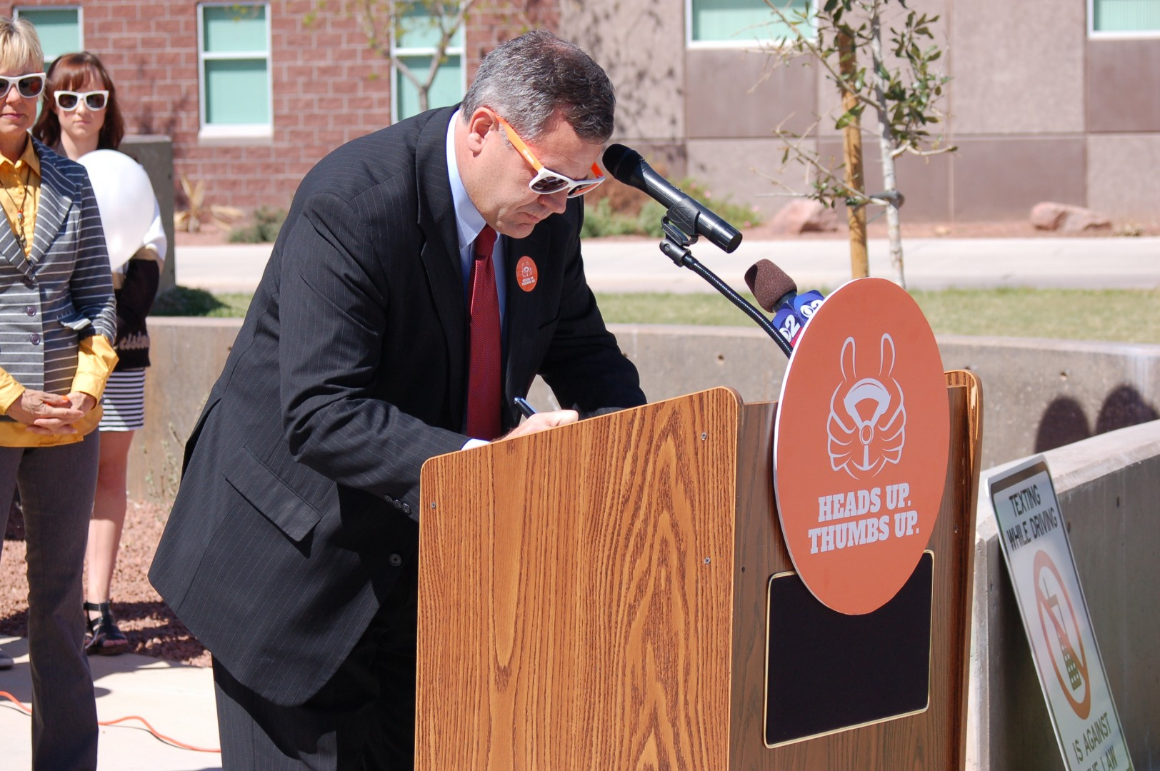 "St. George City Mayor Jon Pike signs a proclamation declaring April as ""Distracted Driving Awareness Month,"" at a press conference at Desert Hills High School, St. George, Utah, April 3, 2014 
