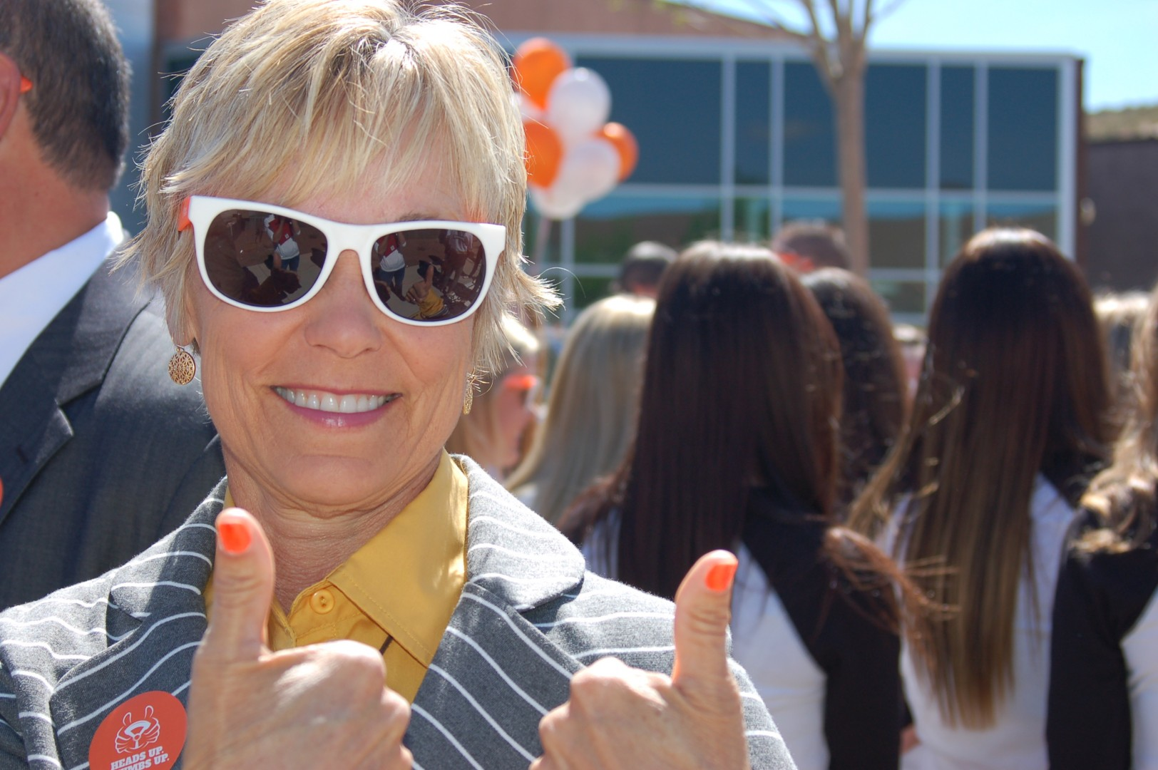 """Leslee Henson, a St. George resident whose husband was killed by a distracted driver a year ago, shows off her orange thumbnails promoting """"Heads Up, Thumbs Up Day,"""" at a press conference at Desert Hills High School, St. George, Utah, April 3, 2014 