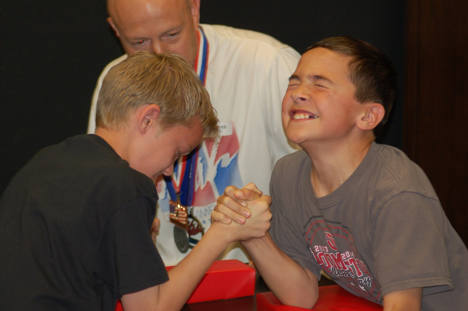 L-R Gage Baresco, 11, Jeff Kirby, and Ian Burge, 11. Baresco and Burge arm wrestle while Kirby referee's at an assembly held at Bloomington Elementary to promote arm wrestling as a sport in the Utah Summer Games, St. George, Utah, April 4, 2014 | Photo by Hollie Reina, St. George News