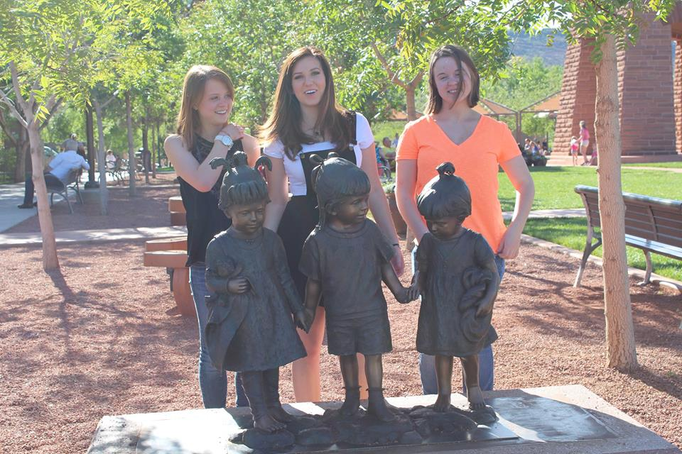 L-R, Megan Dunn, McKenzie Adams, Wendy Dunn, pose behind the statue that they provided the inspiration for as children. The sculpture is on display in St. George Town Square, St. George, Utah, April 12, 2014 | Photo by Amber Green, St. George News