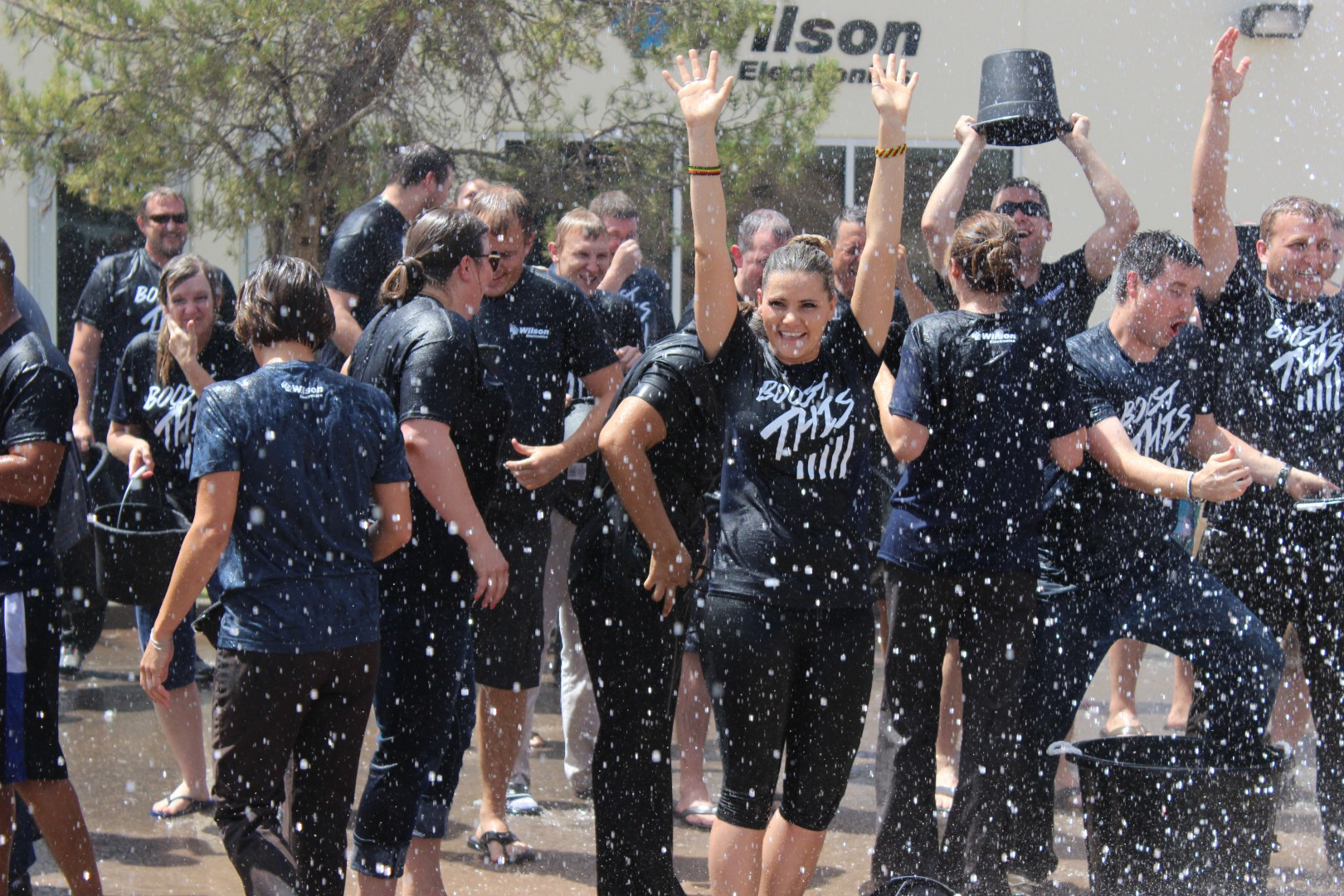 Staff members of Wilson Electronics laugh and scatter as rain from the St. George Fire Department fire truck rains down on them in St. George on Aug. 21, 2014 | Photo by Devan Chavez, St. George News
