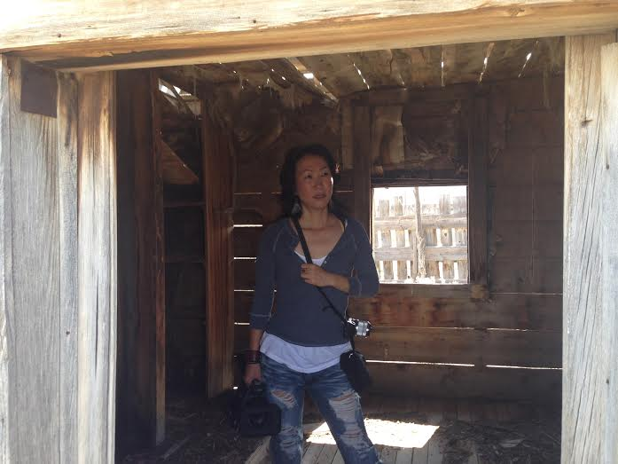 "Mitsuyo Miyazaki, director of ""Where We Begin,"" glances around a the remains of a building while scouting out locations for her film. Cedar City area, Utah, Summer 2014  