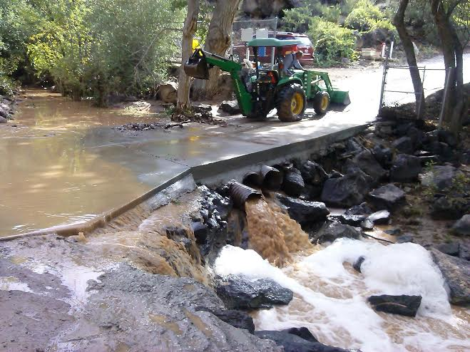 Owner of Veyo Pools Morris Atwell uses heavy equipment to clear standing water and trees that are blocking the flow of the Santa Clara River after the flash flood that swept through the campground in Crawdad Canyon near Veyo Pools in Veyo, Utah, Aug. 2, 2014 | Photo by Aspen Stoddard, St. George News