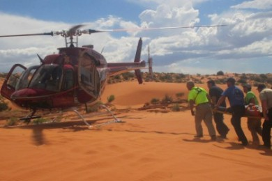 The search and rescue team and some of the Classic Lifeguard crew take Zimmerman to the helicopter for transport, in a mock training episode at  Sand Hollow State Park, Hurricane, Utah, Sept. 20, 2014 | Photo by Mori Kessler, St. George News