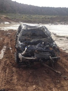 The car carrying the two Italian visitors sits upturned on the bank of the Paria River on Sept. 28, 2014 | Photo courtesy of Garfield County Sheriff's Office, St. George News