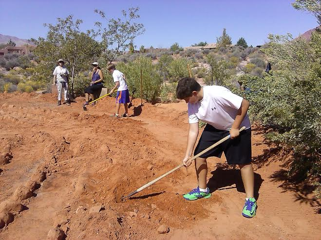 Tate Simpson scrapes dirt away from the rocks at the Desert Rose Labyrinth Sculpture Garden in Kayenta, Utah, Sept. 19, 2014 | Photo by Aspen Stoddard, St. George News