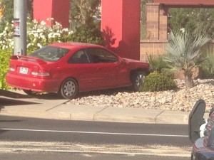 A red Honda Civic crashes into the Red Rock Commons sign after running a red light and being hit by an oncoming car, St. George, Utah, Oct. 23, 2014 |Photo by Holly Coombs, St. George News