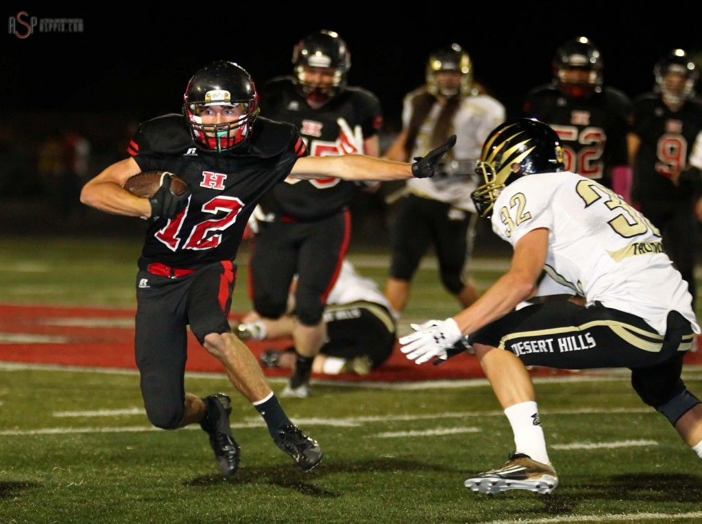 Hurricanes Noah Elison puts a stiff arm on  Zak Fuchs, Desert Hills vs. Hurricane,  St. George, Utah, Oct. 24, 2014 | Photo by Robert Hoppie, ASPpix.com, St. George News