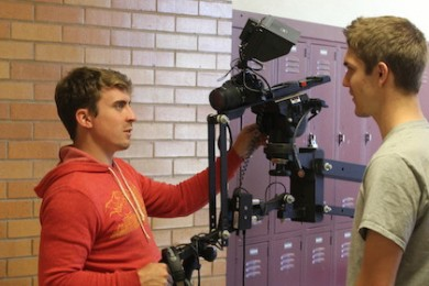 "Joe Cowan (left) and Royce Gillins (right) prepare a camera for production on the set of ""Triangle Power"" at Cedar City High School, Cedar City, Utah, Oct. 14, 2014 