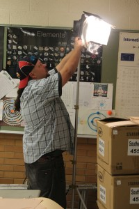 """Haven Scott, Key Grip for """"Triangle Power,"""" prepares some set lights for production in Cedar City High School on Oct. 14, 2014 