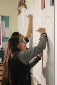 """Casey Velarde, key wardrobe for the production, and Kelcy Faimalo, makeup and hair, draw some shapes on a whiteboard for the production of """"Triangle Power"""" in Cedar City High School on Oct. 14, 2014 