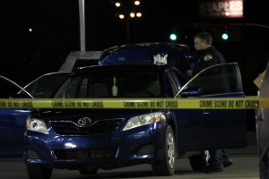 A member of the Cedar City Crime Scene Unit takes pictures of the blue Mazda involved with the _____  in Cedar City on Oct. 21, 2014   Photo by Devan Chavez, St. George News