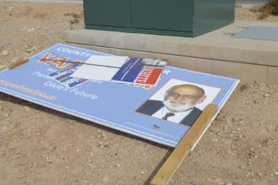 A campaign sign for Paul Van Dam laying behind a utility box on the corner of 1450 S. River Road, St. George, Utah, Oct. 25, 2014 | Photo courtesy of Lisa Rutherford, St. George News