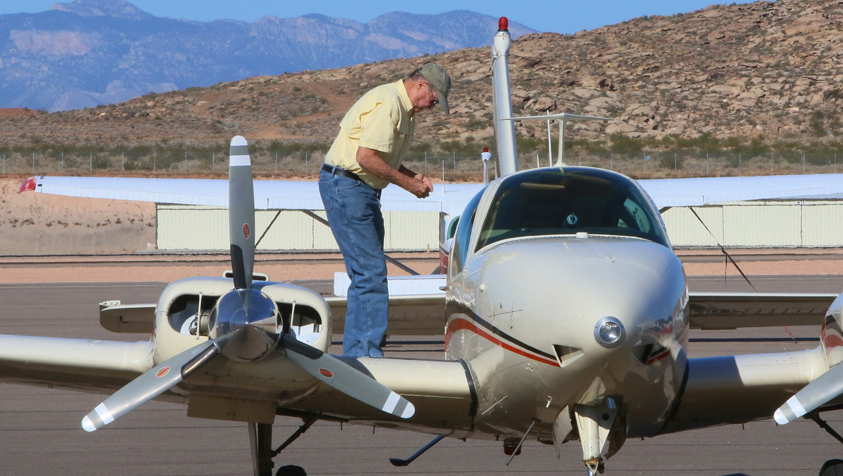 Pilot Bill Williams examines plane after landing  safely after dealing with landing gear that for a time would not engage on his Beechcraft Baron, St. George Municipal Airport, St. George, Utah, Oct. 20, 2014 | Photo by Kimberly Scott, St. George News