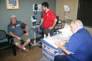 Don Furrow receives help from Tyler Argyle, an SUU health student, and Dr. Rox Burkett, MD., Doctors' Volunteer Clinic, St. George, Utah, Oct. 14, 2014 | Photo by Brett Brostrom, St. George News