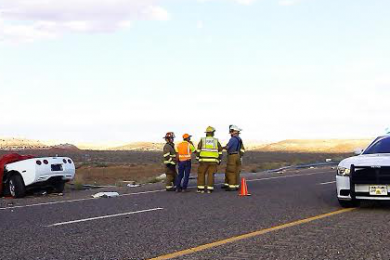 St. George firefighters stand on scene near a Corvette that crashed on state Route 7 just west of the River Road on-ramp, St. George, Utah, Oct. 25, 2014 | Photo by Aspen Stoddard, St. George News