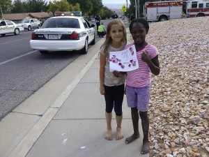 Emily and Jade pose with a thank you picture they designed and gave to the St. George police officers and St. George firefighters on scene at the intersection of 350 N. and 2450 East in St. George, Utah, Oct. 17, 2014 | Photo by Aspen Stoddard, St. George News