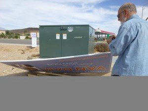 Paul Van Dam retrieves a campaign sign that was removed from the corner of 1450 S. River Road on Oct. 25, 2014 | Photo courtesy of Lisa Rutherford, St. George News