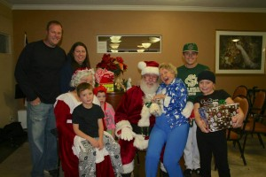A family and a senior pose with Santa during the 2013 santa for seniors event, St. George, Utah,  undated | Photo courtesy of Jennifer Shakespeare, for St. George News