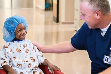 Travis Fullmer, a nurse manager at Valley View Medical Center, talks with a young patient, Cedar City, Utah, date not specified | Photo courtesy of Intermountain Healthcare, St. George News