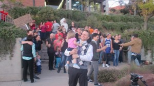 Jared Keddington, Heart of Dixie promoter, carrying his daughter while protesters dance behind him, St. George, Utah, Nov. 6, 2014 | Photo by Mori Kessler, St. George News
