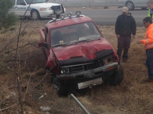 A red Nissan pickup truck sits along Interstate 15 after it ran through the fence and rolled, St. George, Utah, Dec. 31, 2014 | Photo by Holly Coombs, St. George News