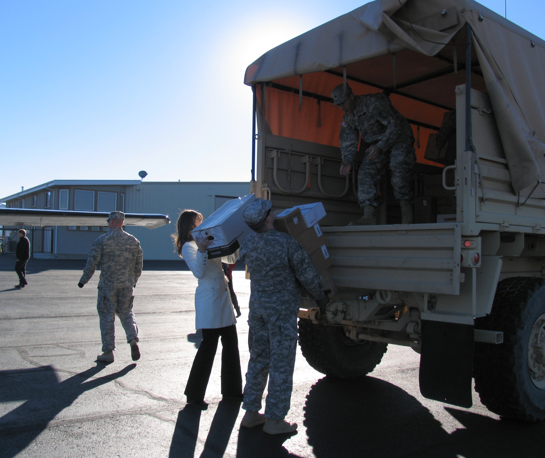Cedar City Mayor, Maile Wilson helps carry donations from the small planes to the LMTV with the 222 Field Artillery Battalion volunteers Tuesday morning   Photo taken by Carin Miller, St. George News