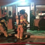 Firefighters cleaning up their equipment after extinguishing a fire at the 1 Stop Laundromat, Dec. 27, 2014, Washington, Utah | Photo by Brett Brostrom, St. George Utah