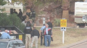 The suspect (gray shirt by the bushes) after surrendering to police. Bruce Solomon can be seen in the  jacket with the gray and red stripes, St. George, Utah, Dec. 2, 2014 | Photo by Mori Kessler, St. George News.
