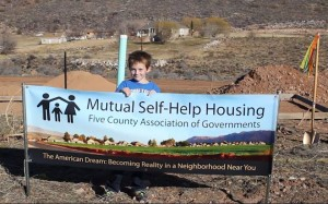 One of the children of a family participating in the program posing in front of a banner at the groundbreaking ceremony, Toquerville, Utah, Jan. 15, 2015 | Photo by Leanna Bergeron, St. George News