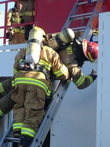 Utah firefighters learn how to help each other down a ladder in an urgent fire situation during a course at Utah Valley University Fire and Rescue Academy's winter fire school program, St. George, Utah, Jan. 9, 2015| Photo by Holly Coombs, St. George News