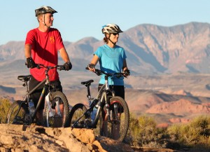 Couple taking a looking at a view as they ride mountain bikes, St. George, Utah, date unspecified | Image courtesy of Adventure Hub, St. George News