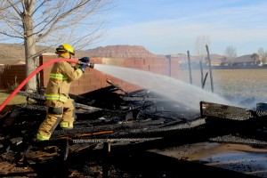 A Washington A Washington City Firefighter sprays water on the remains of a shed that caught fire Monday afternoon after wind reignited the remains of an agricultural burn, Washington City, Utah, Feb. 16, 2014 | Photo by Devan Chavez, St. George News