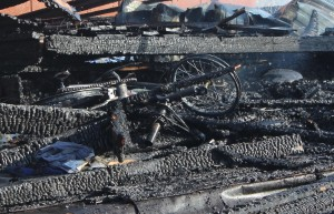 The remains of a bike lay in ashes after firefighters extinguish a structure fire, Washington City, Utah, Feb. 16, 2015 | Photo by Devan Chavez, St. George News