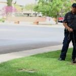 Washington City Police K-9 Handler Josh Finona looks on as police K-9 Hunter lays in the grass outside the Washington City Police Department, Washington City, Utah, March 31, 2015   Photo by Devan Chavez, St. George News