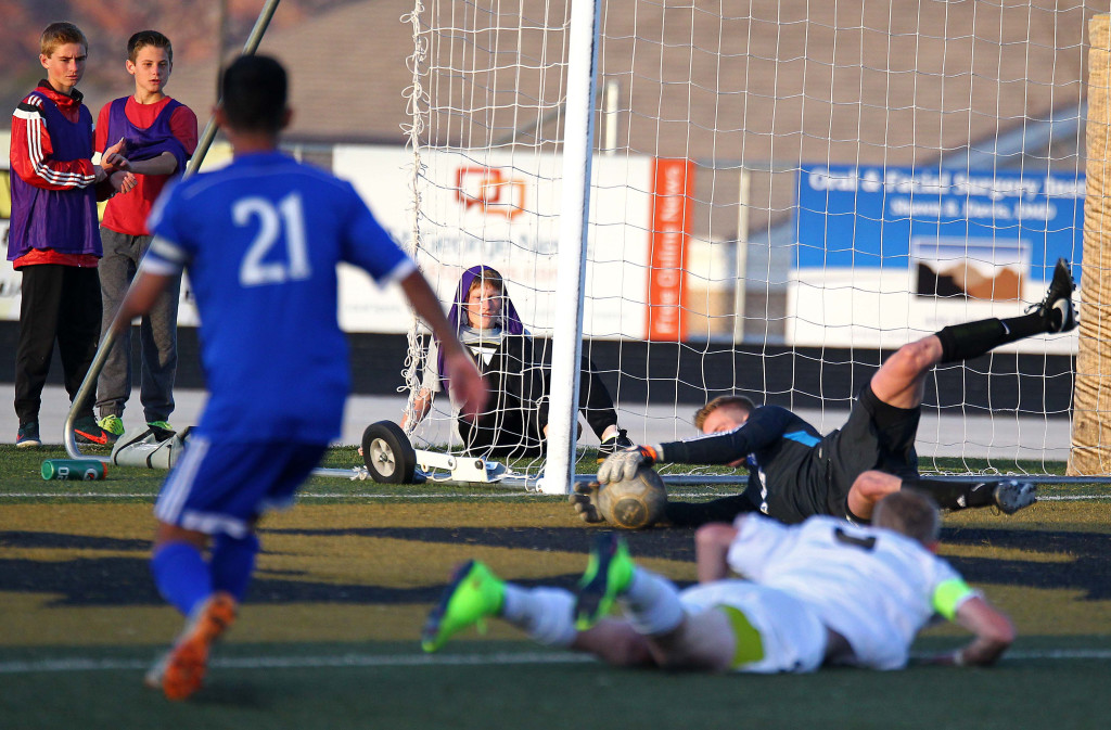 Desert Hills Trevor Browning fires a shot, Dixie goalie Ethan Poulton makes a diving save, file photo from Dixie vs. Desert Hills, Boys Soccer, St. George, Utah, Mar. 10, 2015 | Photo by Robert Hoppie, ASPpix.com, St. George News