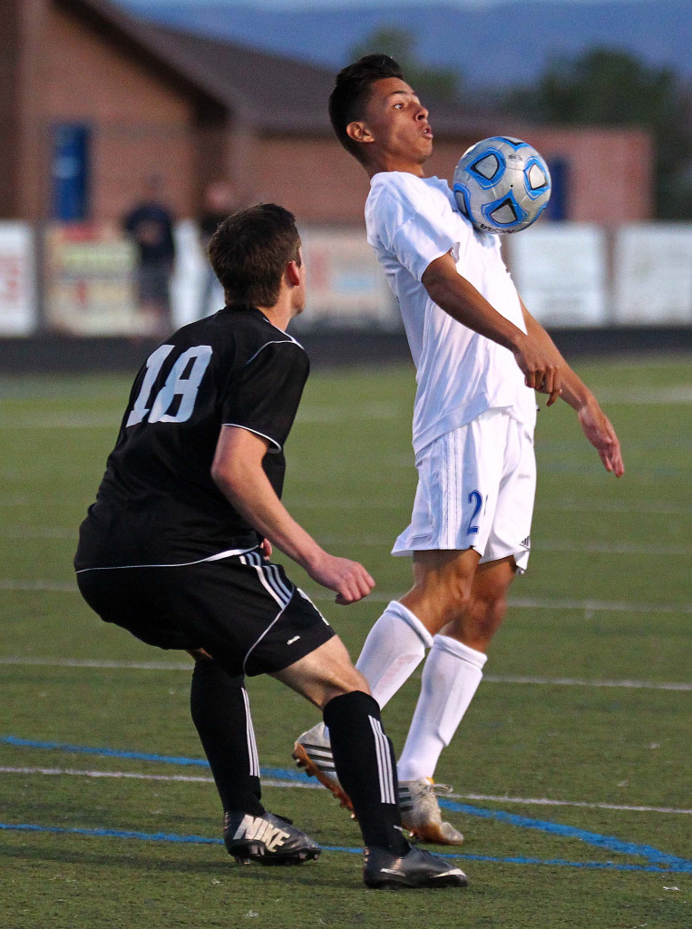"""Jose """"Pepe"""" Garcia (white jersey) takes control of the ball for Dixie in front of jace Fowler, Canyon View vs. Dixie, Boys Soccer, St. George, Utah, Mar. 12, 2015   Photo by Robert Hoppie, ASPpix.com, St. George News"""