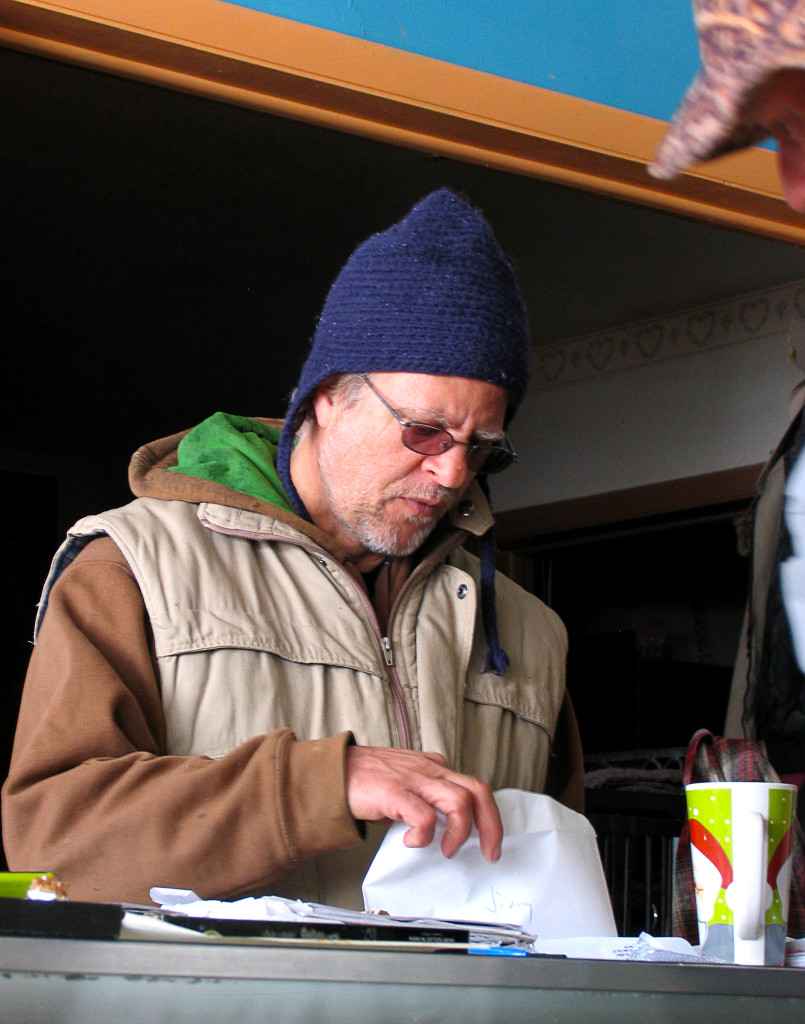 """Owner """"Mystic Mike"""" Ginsburg takes a moment to help a boarder, Mystic Hot Springs, Monroe, Utah, March 2, 2015 