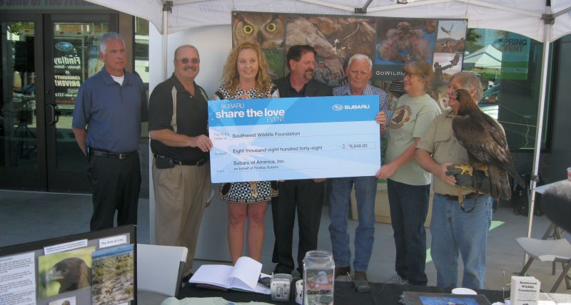 Martin Tyner, CEO and founder of the Southwest Wildlife Foundation, far right, accepts a check from Christina John of Subaru of America, third from left, March 27, 2015 | Photo by Ric Wayman, St. George News