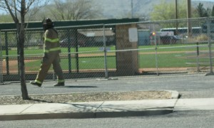 A firefighter in full gear heads toward a beehive at Elks Field Friday | Photo by Ric Wayman, St. George News