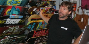 Kris Ripplinger, owner of Lip Trix in St. George, shows a selection of boards to a customer Friday morning | Photo by Ric Wayman, St. George News
